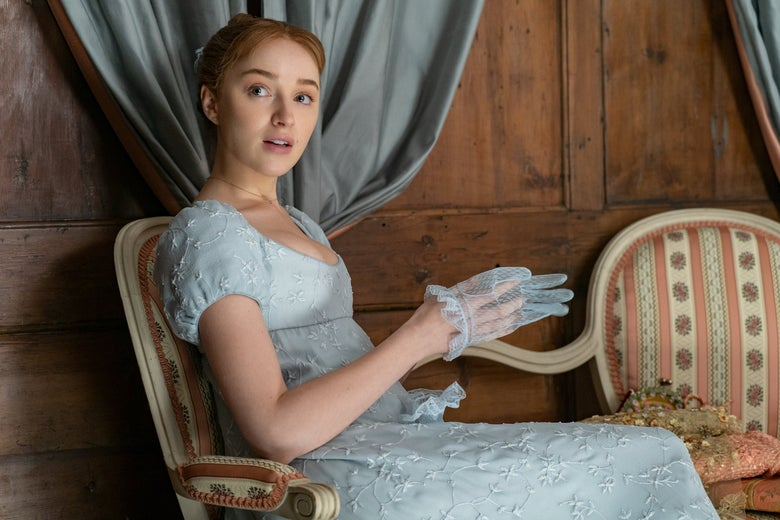 Phoebe Dynevor sits in a chair glancing over her shoulder. One hand is halfway in a translucent blue glove.