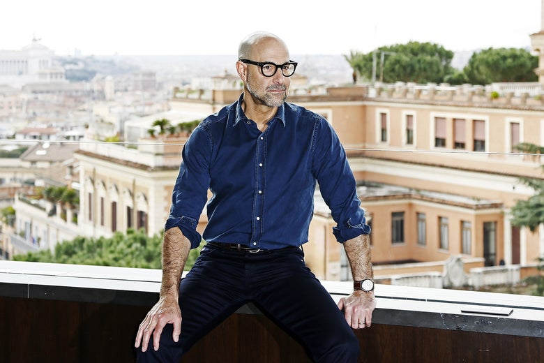 Stanley Tucci sitting on a ledge overlooking Italian buildings, his sleeves rolled up to reveal his famous forearms.