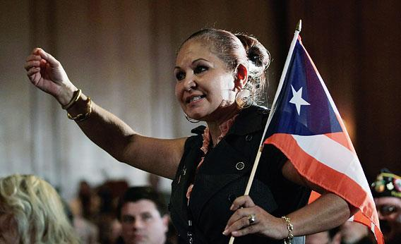 Elizabeth Cuevas-Neunder holds a Puerto Rican flag as she directs a question to Republican presidential candidate and former Speaker of the House Newt Gingrich after he was endorsed by the National Hispanic Leadership Network at the Doral Golf Resort and Spa on January 27, 2012 in Miami, Florida. Gingrich is campaigning ahead of Florida's January 31, primary.