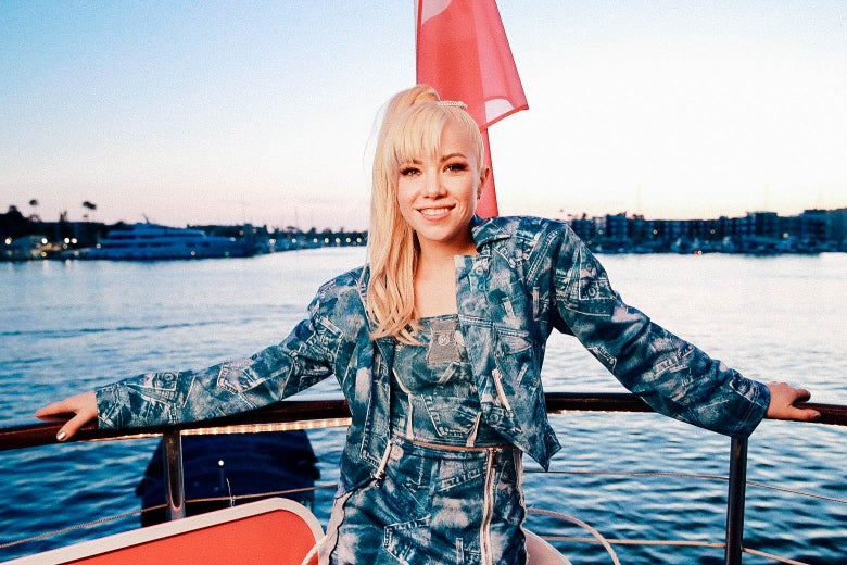 Carly Rae Jepsen in an all-denim outfit on a boat in a harbor.