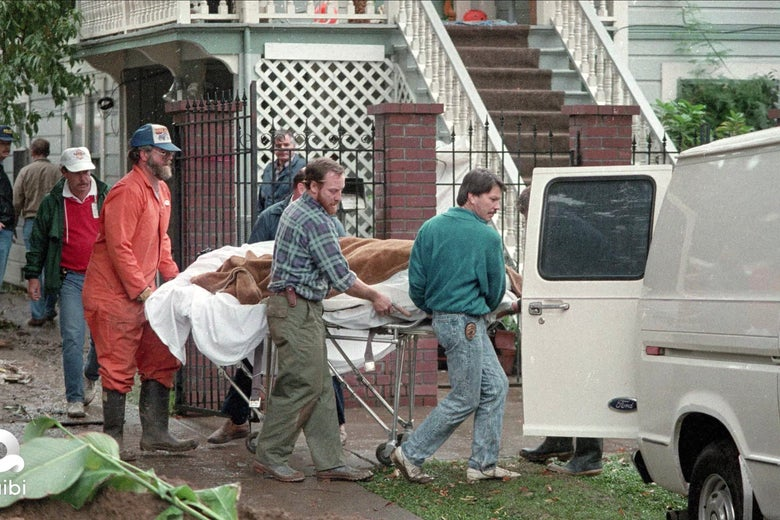 What appears to be a body loaded into a van in a body bag
