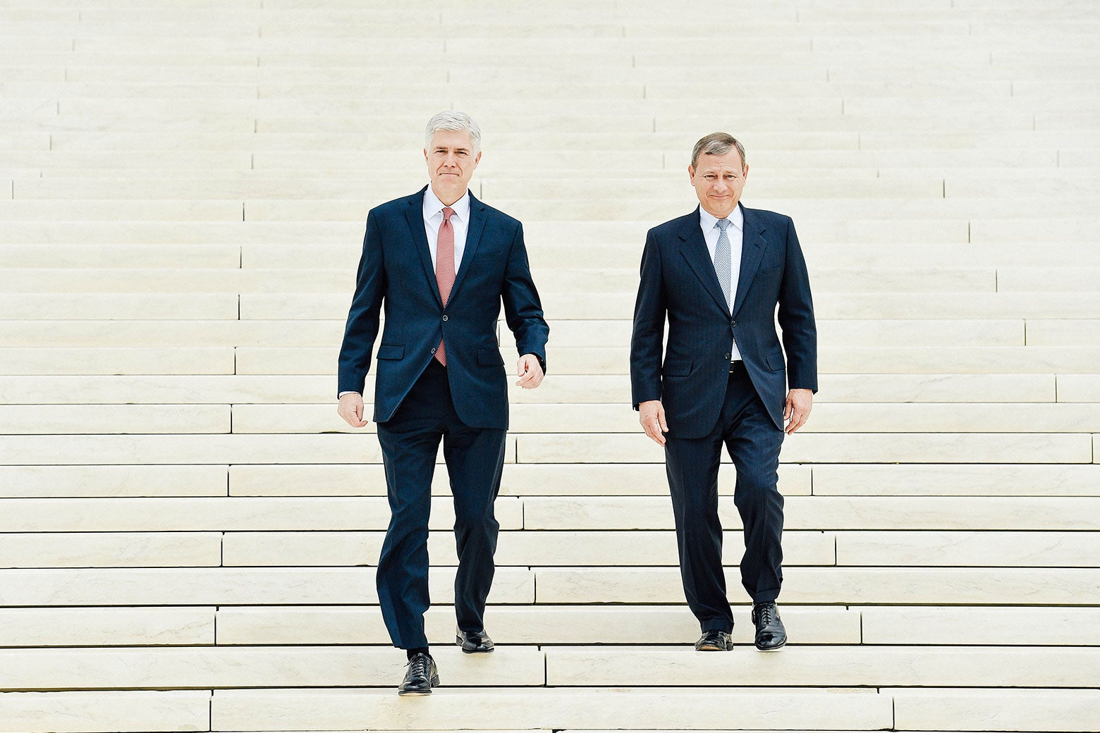 A wide shot of the Supreme Court steps as Gorsuch and Roberts walk down them