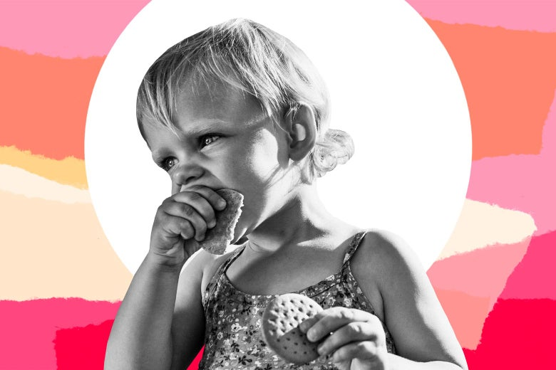 A child eating a cracker while holding another cracker