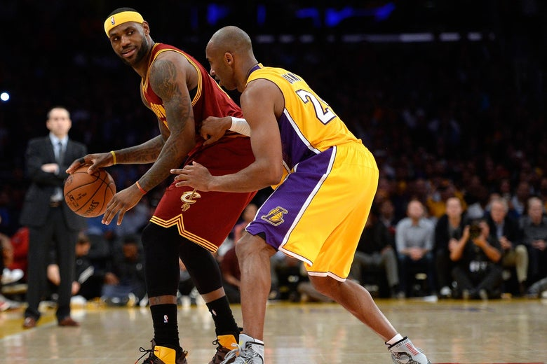 LeBron James of the Cleveland Cavaliers dribbles as he is guarded by Kobe Bryant.