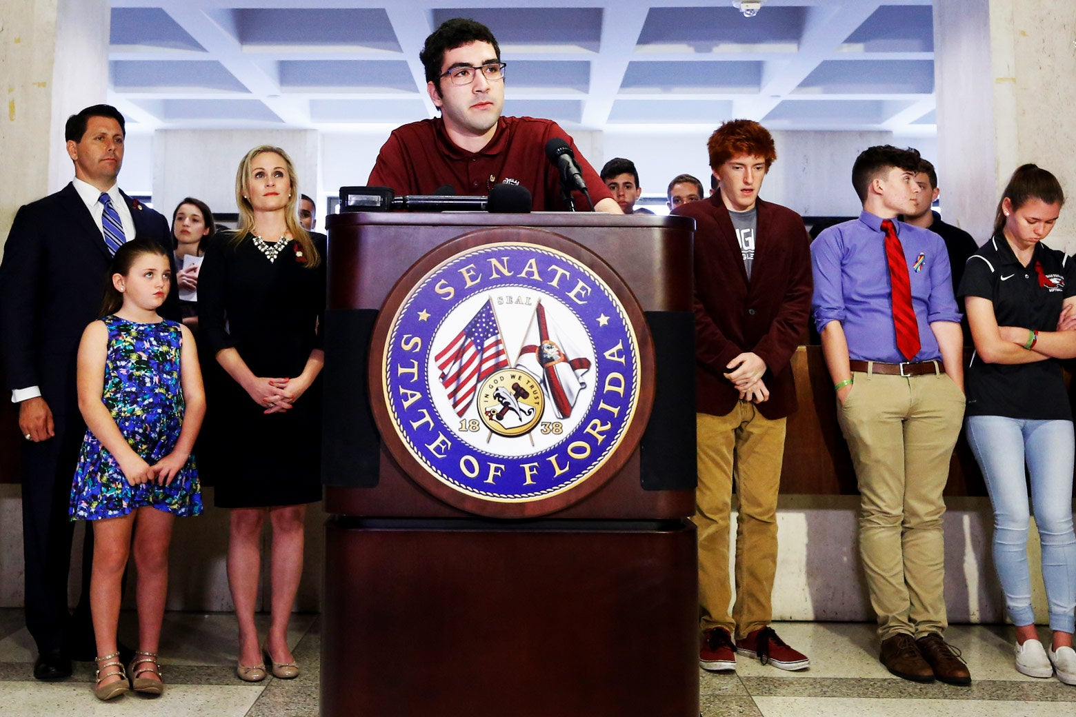 Lorenzo Prado stands at a podium with fellow survivors and family members behind him.
