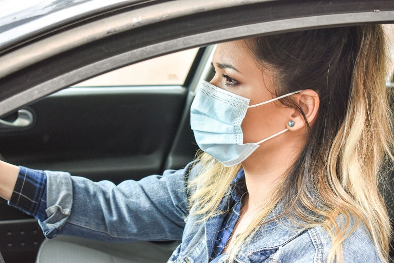 A woman wearing a surgical mask, sitting at the wheel of a car