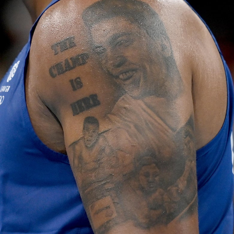 """The tattoo on an arm showing three Muhammad Alis and reading """"The Champ Is Here"""" at the top, torso in a singlet."""