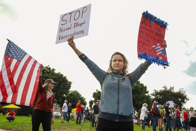 A woman holds up anti-vaccine protest signs.