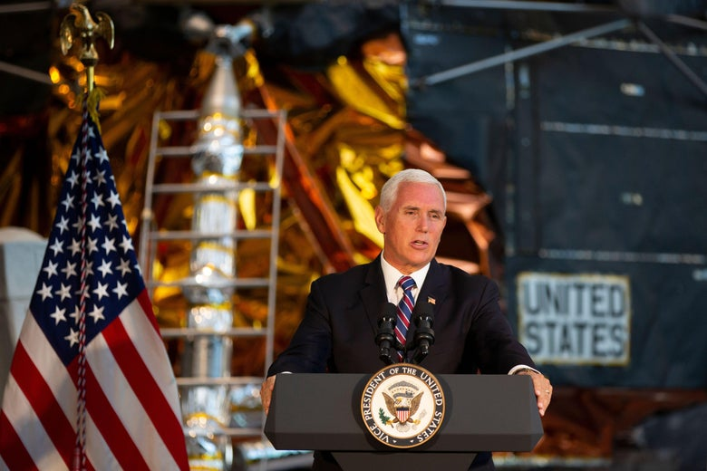 Pence stands before a podium, with the American flag and spacecraft in the background.
