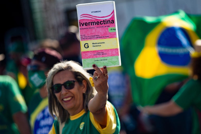 A woman holds a large box of box of ivermectin while someone behind her unfurls a Brazilian flag.
