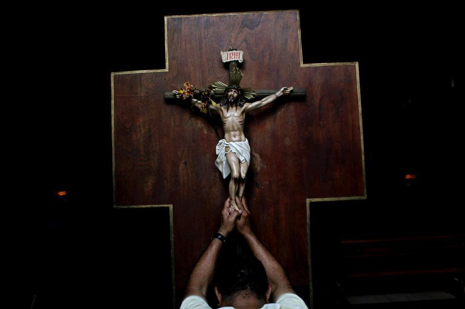 A man prays as he touches a crucifix at La Candelaria church in Caracas, Venezuela, on March 13, 2013. Latin Americans reacted with joy on Wednesday at news that Argentine Cardinal Jorge Bergoglio has become the first pope ever from the Americas and the first from outside Europe in more than a millennium.