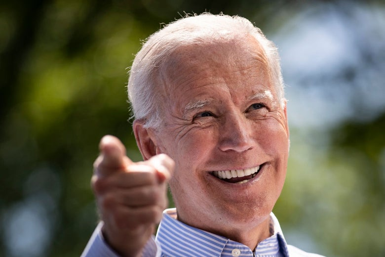 Biden, wearing a button-down shirt without a jacket, points to his right while smiling.
