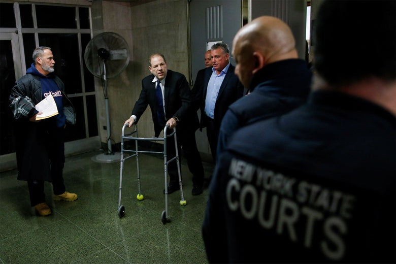 Weinstein, aided by a walker, exits a courtroom at the New York Supreme Court.