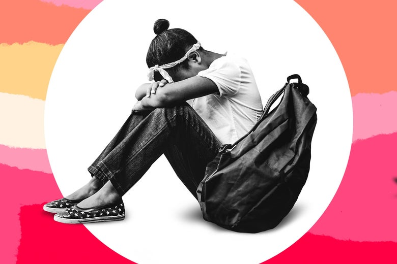 A girl with her head down, crying, next to a backpack.