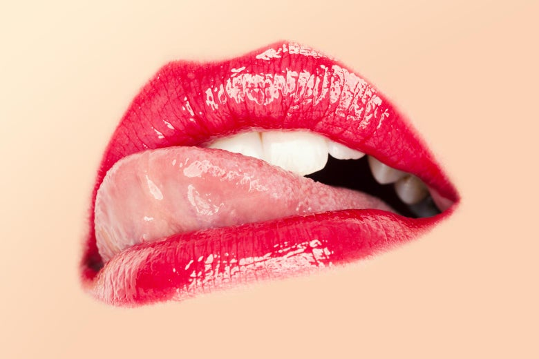 Close-up on the mouth of a woman licking her red glossy lips