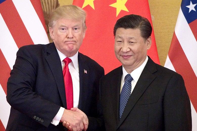 Donald Trump and Xi Jinping, standing, shake hands.