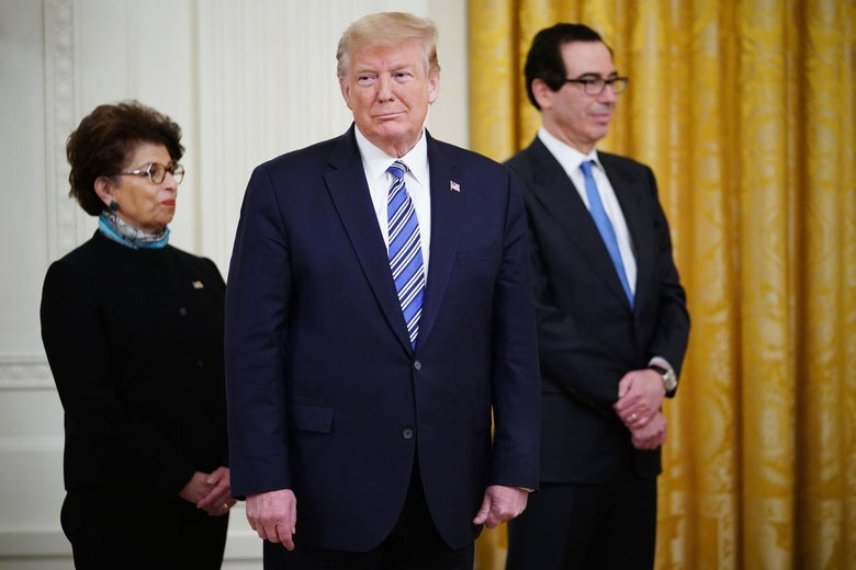 US President Donald Trump (C) is flanked by Small Business Administration Administrator Jovita Carranza (L) and Treasury Secretary Steven Mnuchin during a press briefing in the East Room of the White House in Washington, DC, on April 28, 2020. - US President Donald Trump held a press briefing about supporting small businesses during the coronavirus pandemic through the Paycheck Protection Program. (Photo by MANDEL NGAN / AFP) (Photo by MANDEL NGAN/AFP via Getty Images)