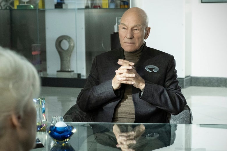 Patrick Stewart sits with his hands folded at a desk across from a white-haired woman seen from behind.