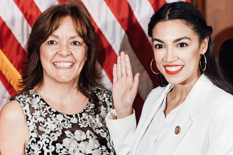 Blanca Ocasio-Cortez and Alexandria Ocasio-Cortez stand side by side against an American flag. AOC raises her right hand.