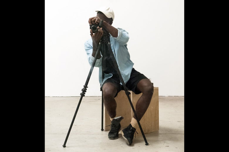 A casually dressed young black man is taking a photograph. The camera is on a tripod.