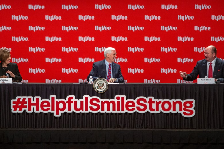Kim Reynolds, Mike Pence, and Randy Edeker sit spaced apart on a panel that says #HelpfulSmileStrong