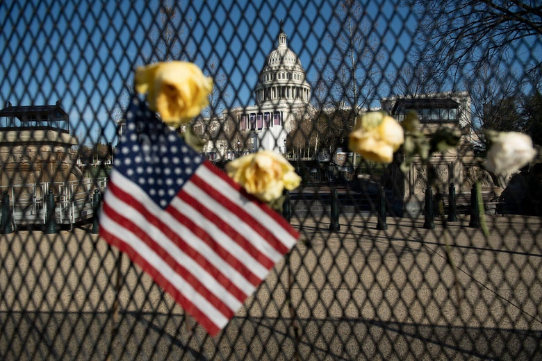 Flowers are placed on a fence, next to an American flag, outside of the Capitol in Washington D.C.