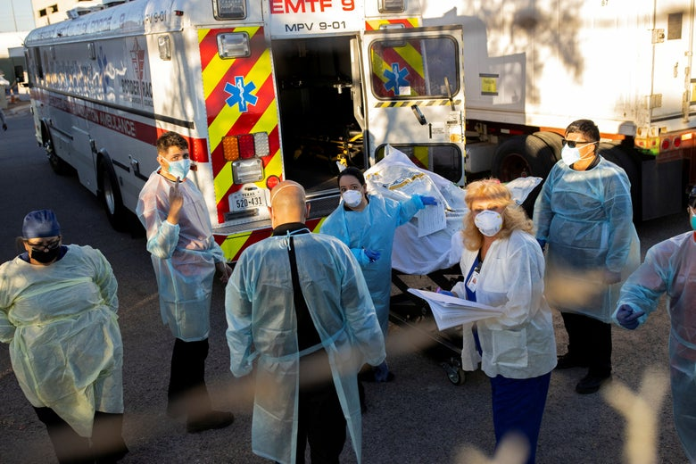 Medical workers in gowns and masks stand outside a refrigerated trailer.
