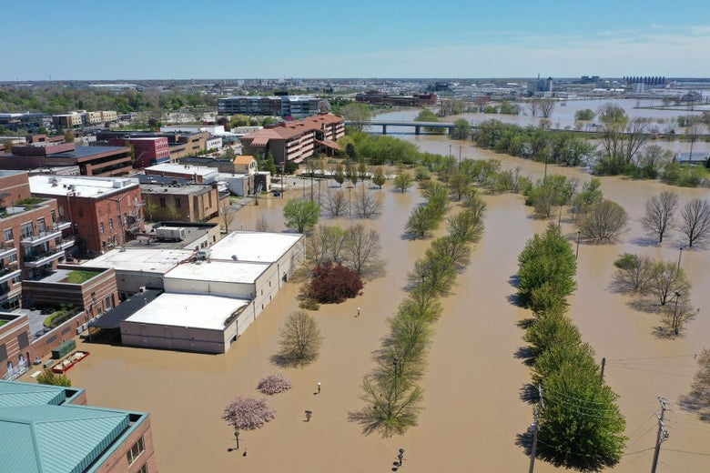 An aerial shot depicts brown river water that has flooded up to the edge of a small-town downtown, submerging buildings and trees.