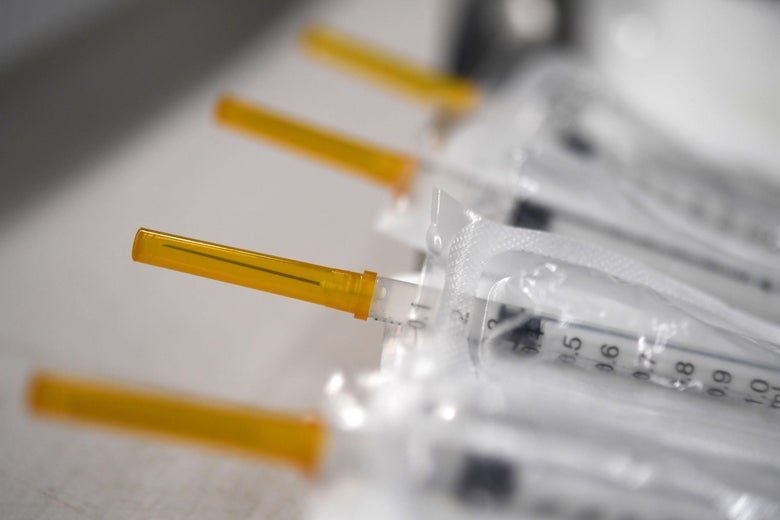 A row of syringes filled with COVID-19 vaccine