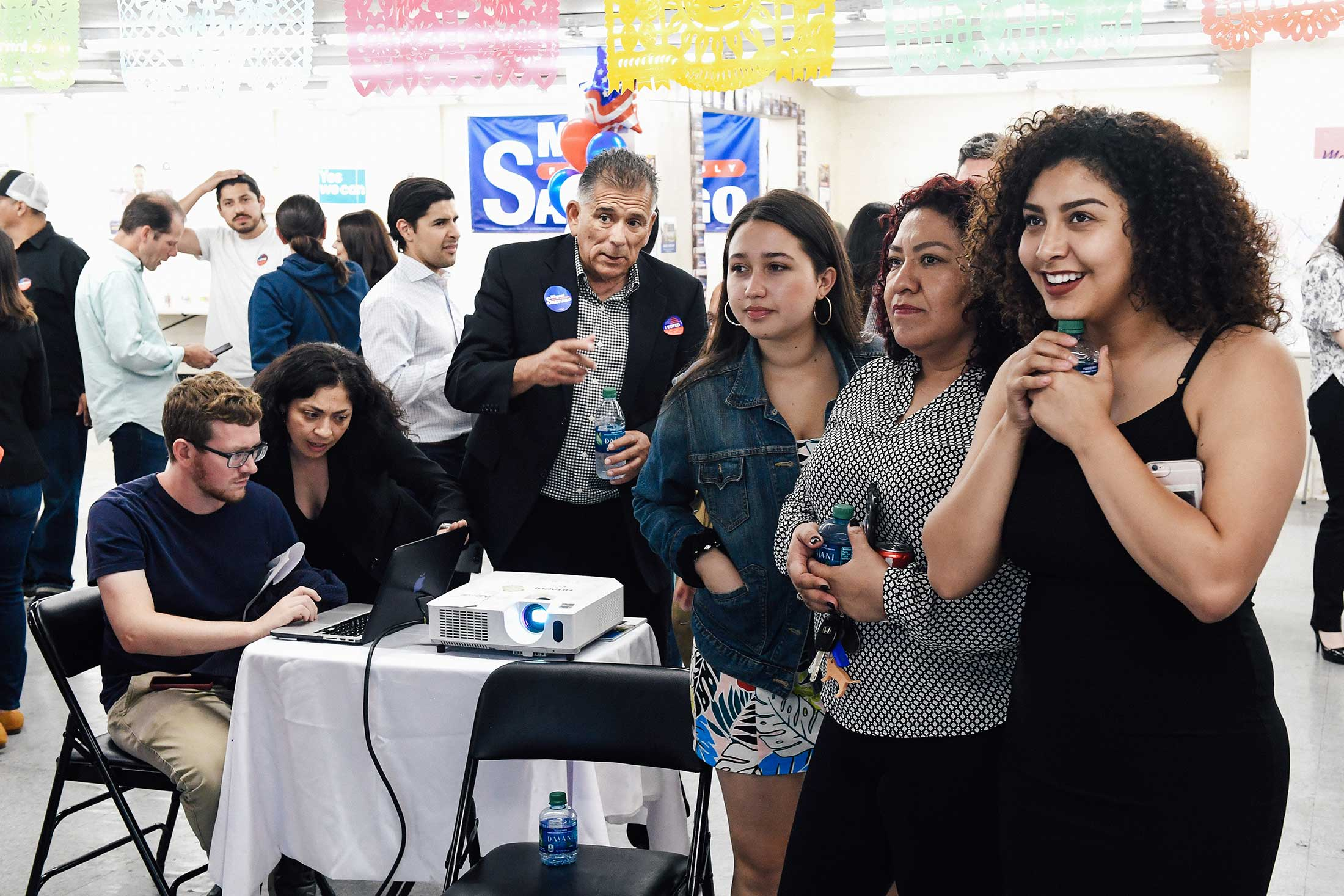 A crowd of excited young people smiling and look upward as if at a television screen