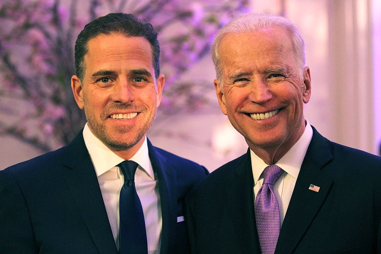 Hunter and Joe Biden smile toward the camera, standing in a room with light purple lighting and a tree in bloom in the background