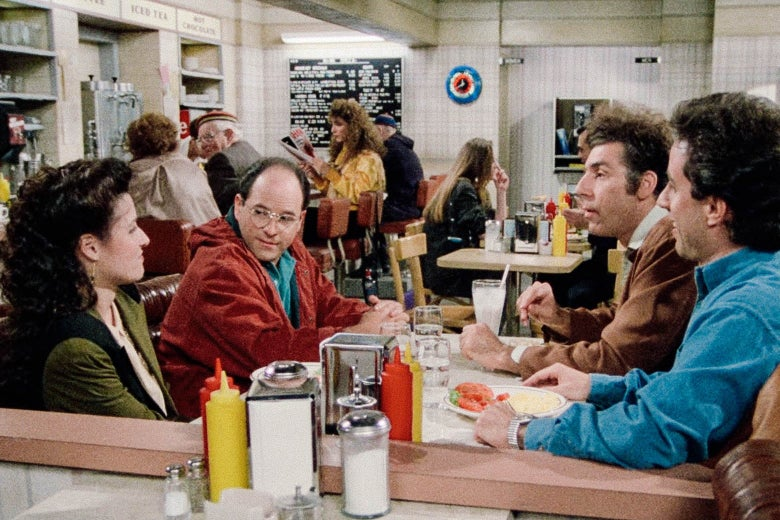 Julia Louis-Dreyfus, Jason Alexander, Michael Richards, and Jerry Seinfeld sit in a diner booth.