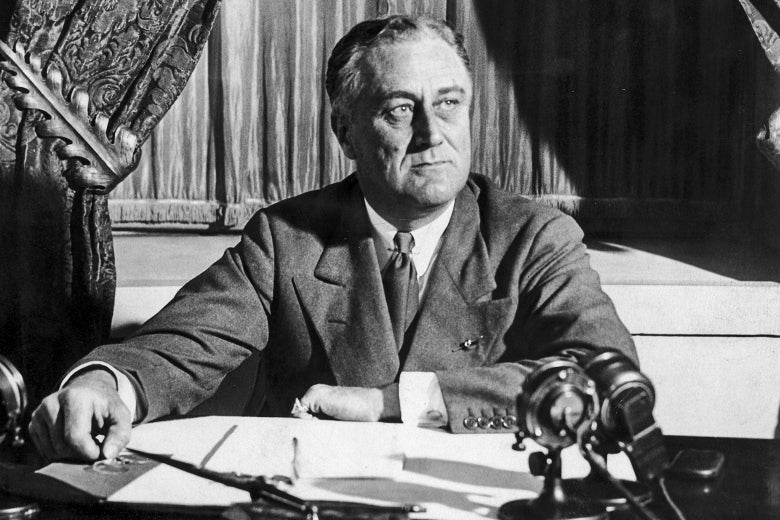 In a black and white photo, Franklin Roosevelt sits at a desk with microphones, probably during a radio broadcast.