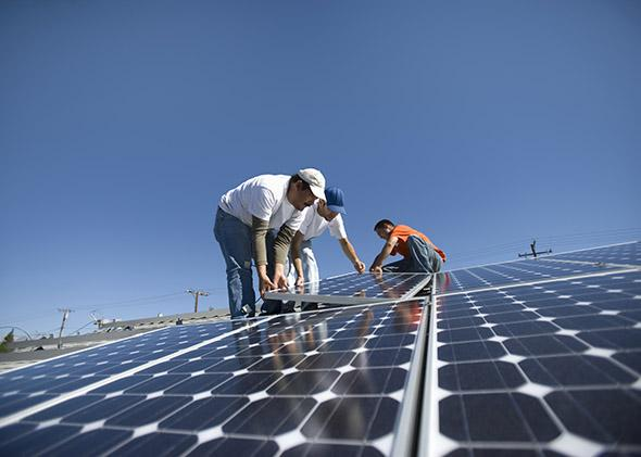 A group of men working on solar panelling.