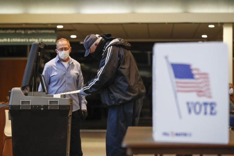 "A man wearing a mask casts a ballot while a masked election worker looks on. A sign in the foreground says ""VOTE"" and features an American flag."