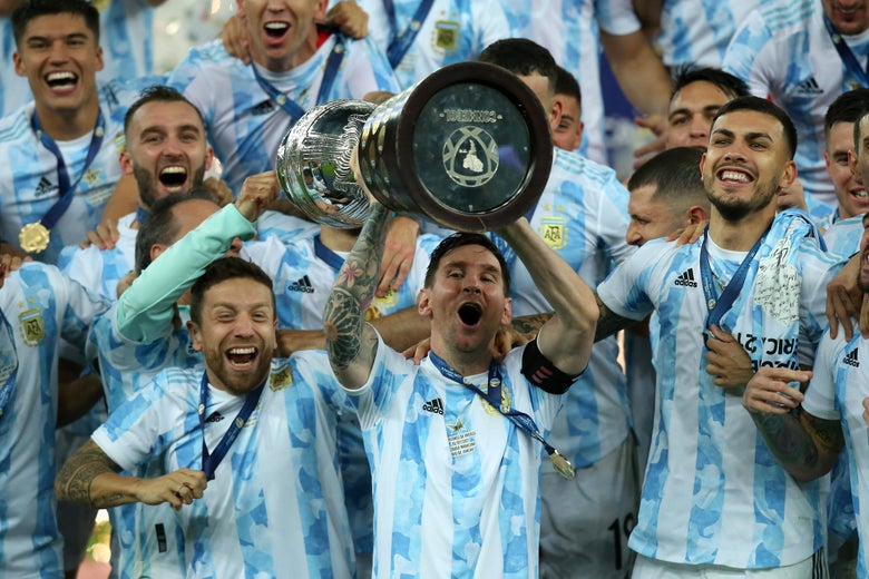 Lionel Messi lifts a trophy surrounded by his Argentinian teammates