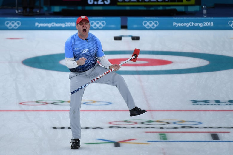 John Shuster, holding his curling broom, stands on one leg and yells in triumph.