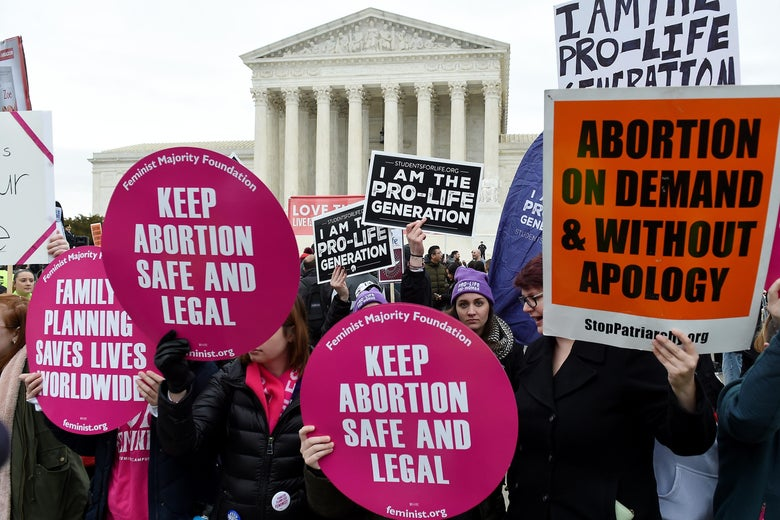 A crowd of protesters holding signs for and against abortion outside the Supreme Court
