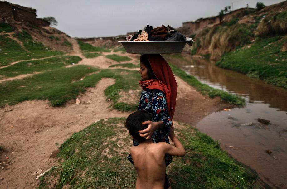 An Afghan refugee girl carries her laundry on her head after washing it in a polluted stream on World Water Day in a poor neighborhood on the outskirts of Islamabad, Pakistan on March 22, 2013.