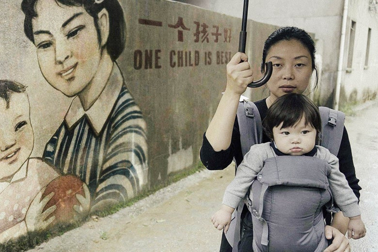 "Still from One Child Nation showing a woman carrying a baby and an umbrella near a wall that depicts the motto ""One Child Is Best"""