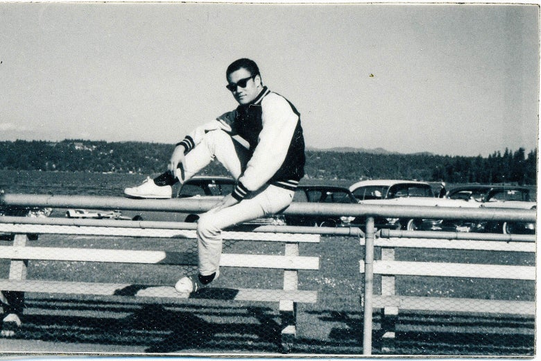 Bruce Lee, looking impossibly cool, sitting on a railing, in sneakers and sunglasses