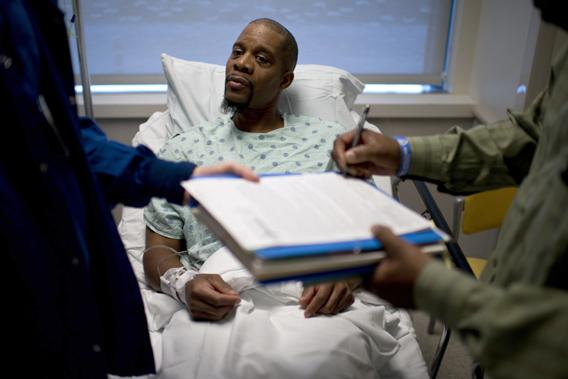 A kidney donor watches as a consent form is singed by a witness before a kidney transplant operation at Johns Hopkins Hospital June 26, 2012 in Baltimore, Maryland.