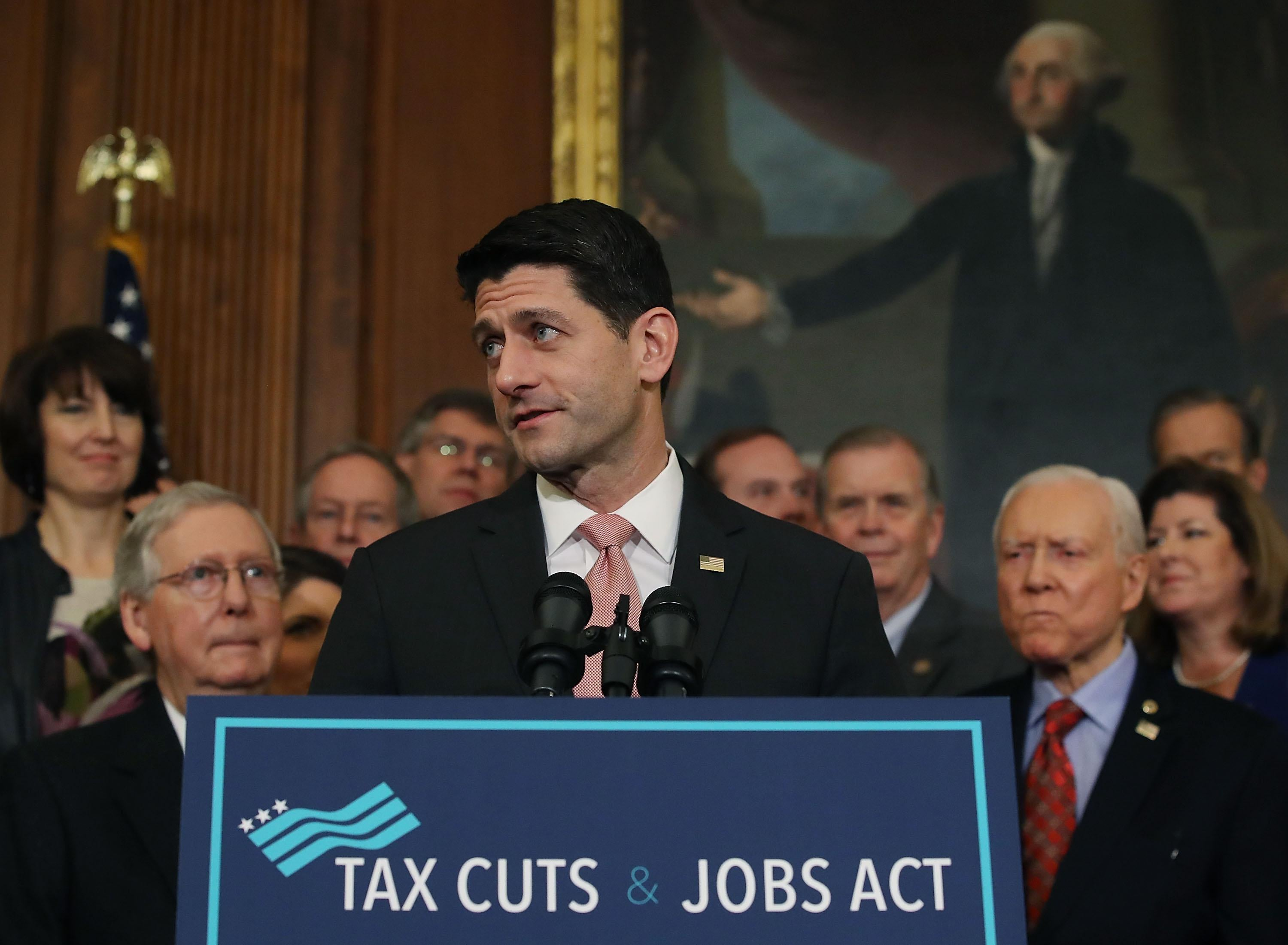 U.S. House Speaker Paul Ryan, flanked by Republican lawmakers, speaks during a ceremony for the conference report to the Tax Cuts and Jobs Act.