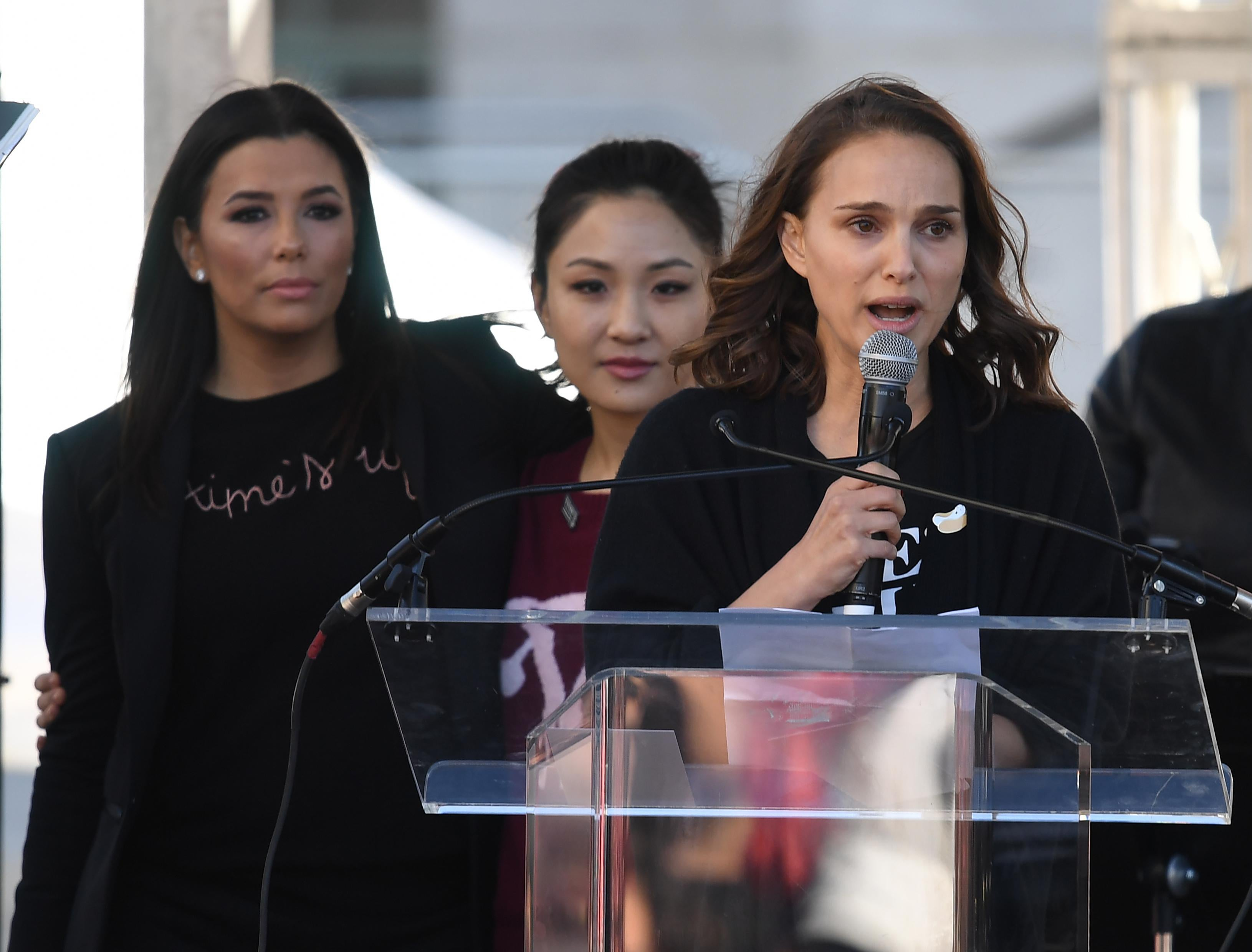 Natalie Portman speaks at a podium while actors Eva Longoria and Constance Wu stand behind her.