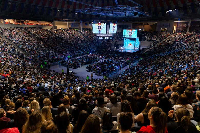 A huge arena filled with Liberty University students. Bob Smiley can be seen on the stage and on large screens in the center of the space.