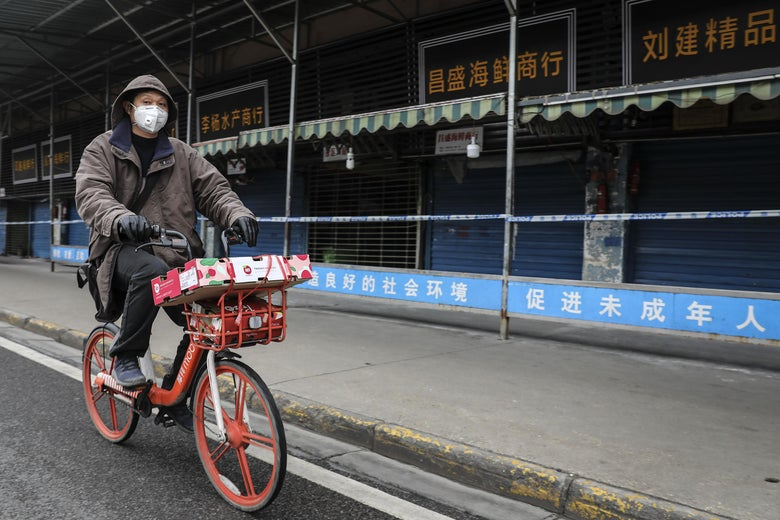 A man wears a mask while riding on a bike past a closed storefront.