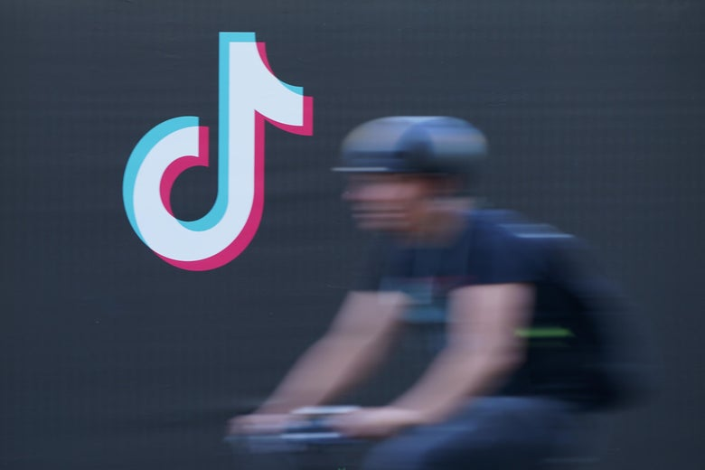 A blurred bicyclist rides past a TikTok advertisement.