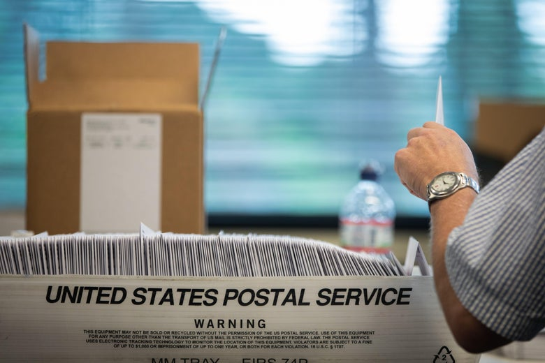 """A box reading """"United States Postal Service"""" is seen full of files. An arm is seen taking one out."""