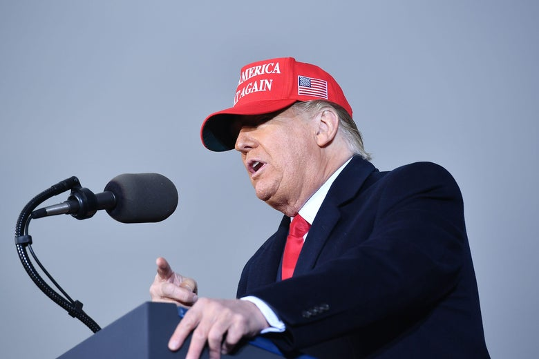 Donald Trump speaks into a microphone at a podium while wearing a red MAGA hat.