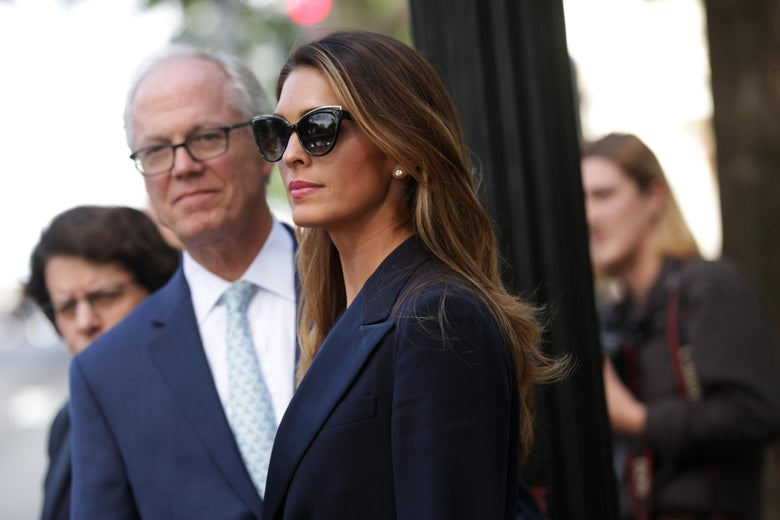 Hope Hicks, wearing sunglasses and a blazer, is standing outside.